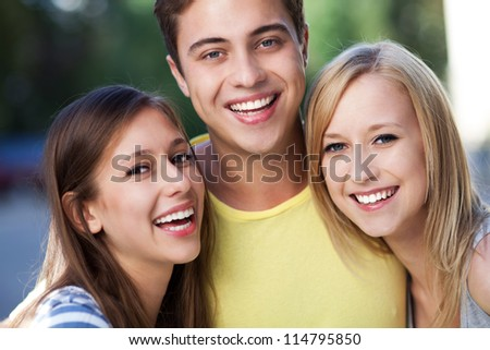 Young man with two female friends - stock photo