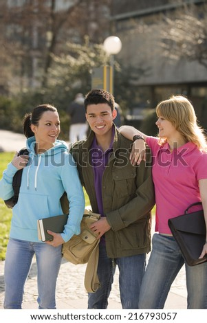 Young man with two young women smiling