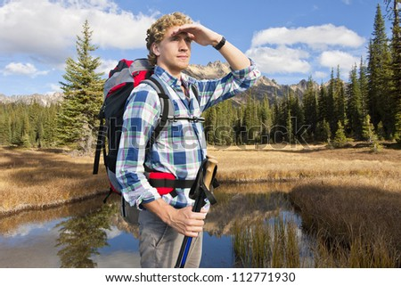 young man with walking sticks and a back pack admires the beautiful scenery in the evening light - stock photo
