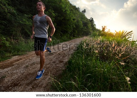Young man with wet singlet running on a rural road during sunset - stock photo