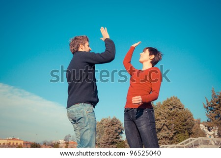 Young Man with Woman Jumping and Giving High Five - stock photo