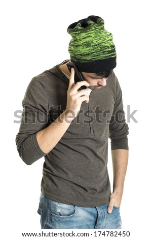 Young man with wool cap talking on the cell phone isolated on a white background