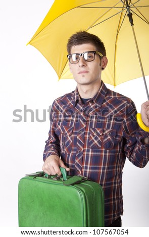 Young man with yellow umbrella holding suitcase. - stock photo