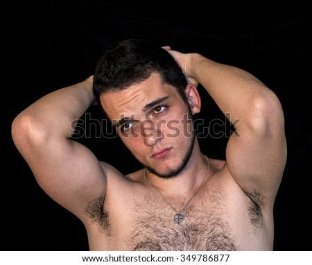 Young man without shirt, hands on head, portrait over black background