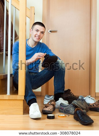 Young man woman cleaning shoes at home