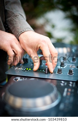 Young man working as dj with mixer. Shallow focus on hands. - stock photo