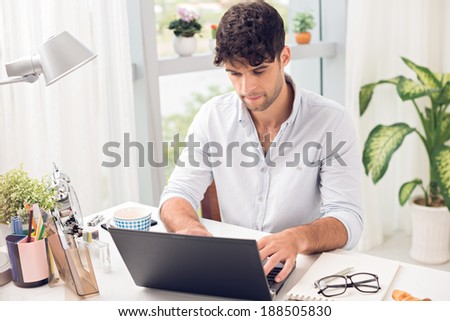 Young man working at home on his laptop - stock photo