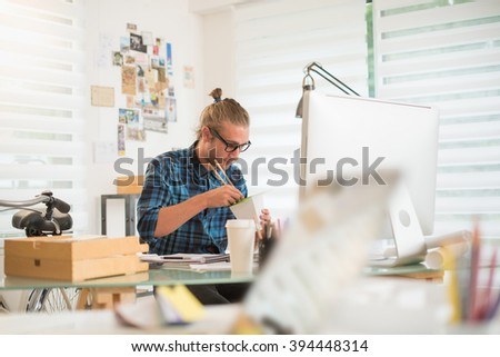 young  man working in an office, eating a lunchbox while working on his computer. Shot with flare - stock photo