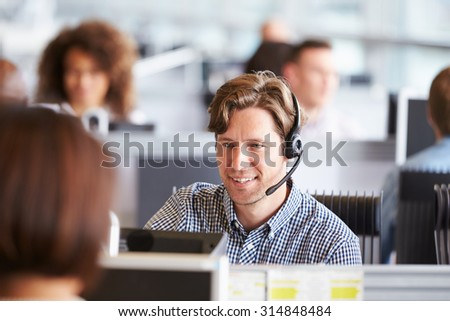 Young man working in call centre, surrounded by colleagues