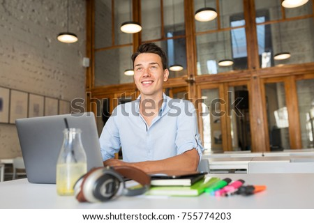 young man working in office room at laptop, smiling, start up