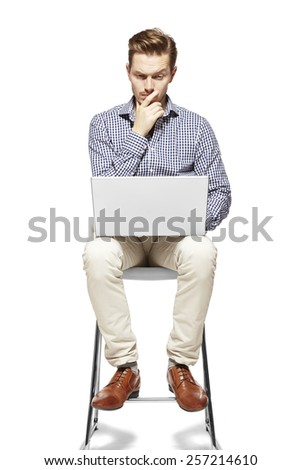 Young man working on a computer and thinking. - stock photo