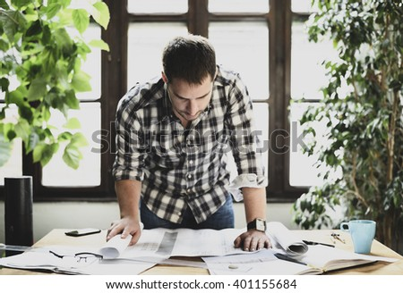 Young man working on architectural project. Modern office concept - stock photo