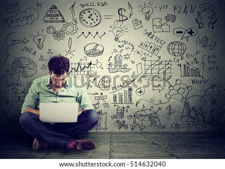 young man working on computer sitting on a floor learning online drawing schemes business plan on a wall