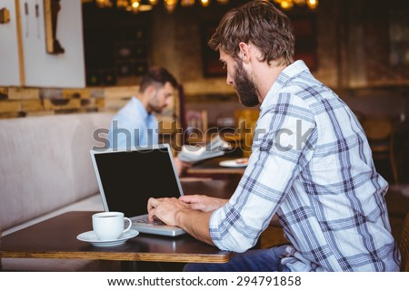 young man working on his computer at the cafe - stock photo