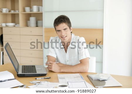 Young man working on his finances in his home's kitchen. - stock photo
