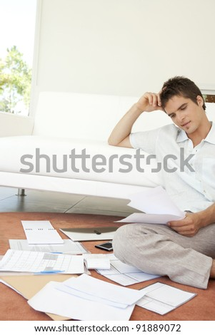 Young man working on his finances, sitting on the floor by the sofa.
