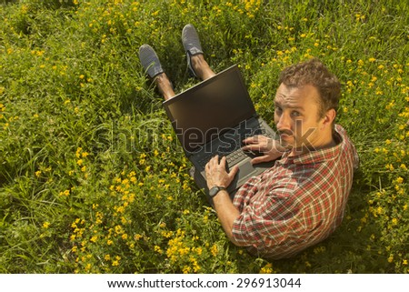 Young man working on his laptop outdoors - stock photo