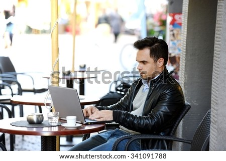 Young man working on laptop in a public open pub or bar and drinking coffee. Busines man using computer in a public place to access social networks and the internet. Education and working concept.