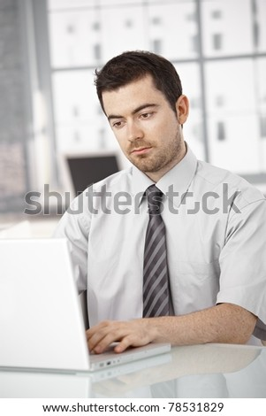 Young man working on laptop in bright office sitting at desk.?