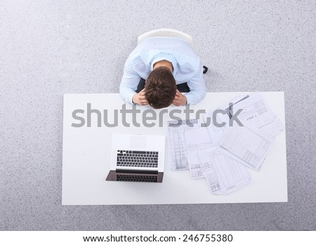 Young man  working on laptop, sitting  the desk in office - stock photo