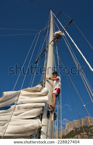 young man working on sailing ship, active lifestyle, summer sport concept - stock photo
