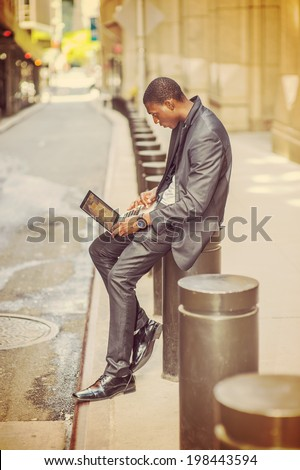 Young man working on street. A young black college student is sitting outside an office building, typing on a laptop computer, reading, thinking.   - stock photo