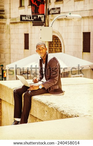 Young man working on street. A young black college student is sitting outside, looking away, thinking, working on a laptop computer. Wall Street sign in the background. - stock photo