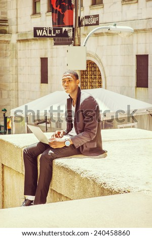 Young man working on street. A young black college student is sitting outside, looking away, narrowing eyes, thinking, working on a laptop computer. Wall Street sign in the background. - stock photo