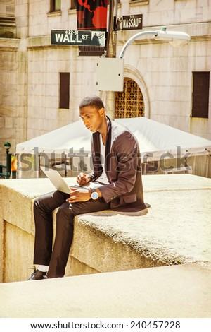 Young man working on street. A young black college student is sitting outside, looking down, working on a laptop computer. Wall Street sign in the background. - stock photo