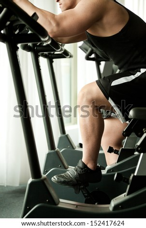 young man working out on bicycle - stock photo
