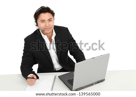 Young man working, with a laptop and headset. Wearing a suit and white shirt. White background. - stock photo