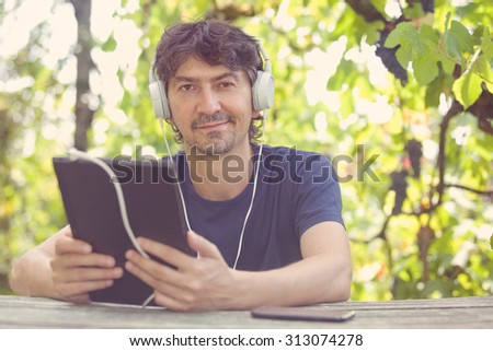 young man working with a tablet pc with headphones, outdoor, filtered image