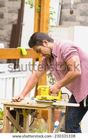 young man working with an electrical sander holding wood plank - stock photo
