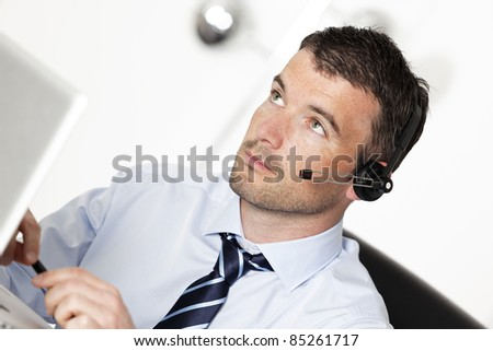young man working with headset in office - stock photo