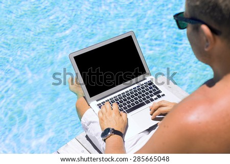 Young man working with laptop computer by the swimming pool - stock photo