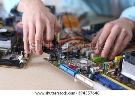 Young man working with pliers in service center - stock photo