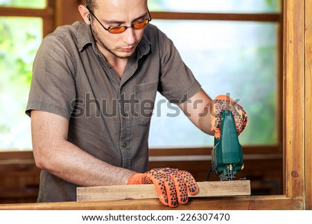 Young man working with wood. Natural background behind
