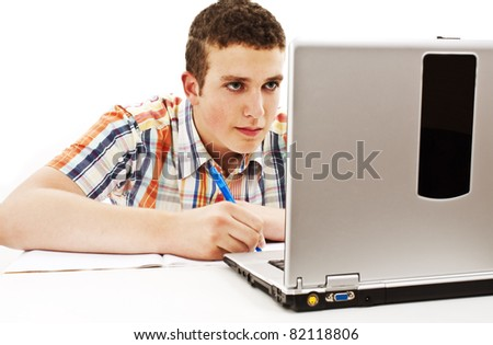 Young man writing and looking to his laptop computer - stock photo