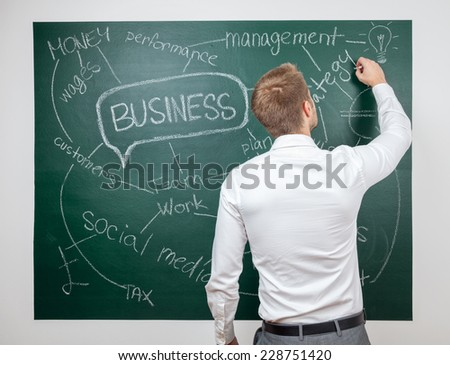Young man writing down business ideas on blackboard - stock photo