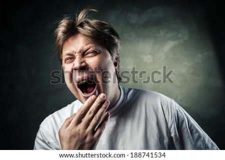 Young man yawning in studio over gray background - stock photo