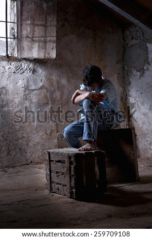 Young man, 12 years, dirty, mistreated, sat in a garret - stock photo