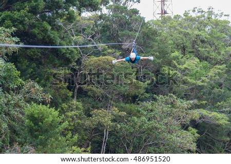 young man zooming thru a cloud forest on a zip line adventure in Monteverde Costa Rica
