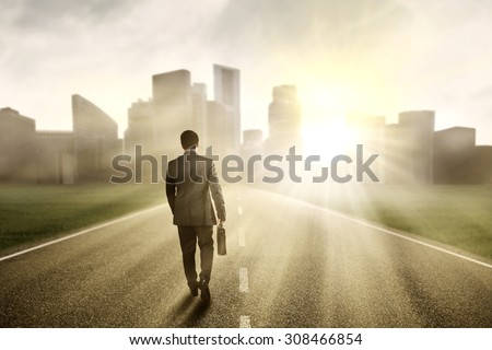 Young manager carrying a briefcase while walking on the road toward a city