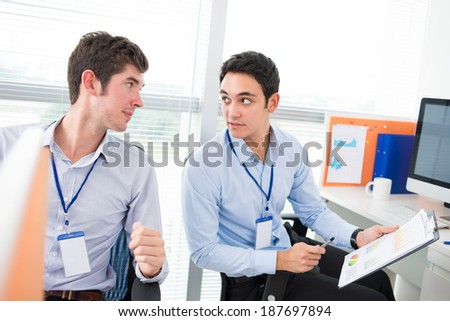 Young manager consulting his colleague - stock photo