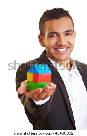 Young manager holding a house made of building bricks