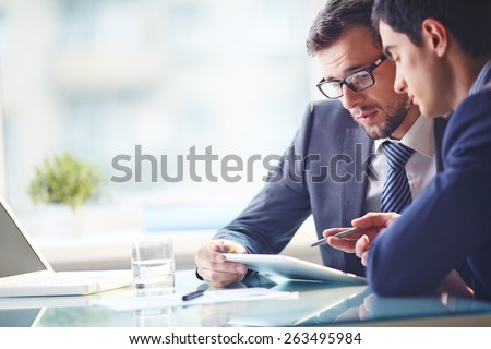 Young manager listening to his colleague explanations - stock photo
