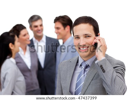 Young manager on phone standing in front of his team against a white background
