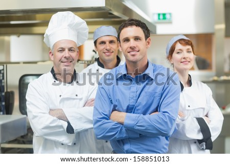 Young manager posing with some chefs in a kitchen