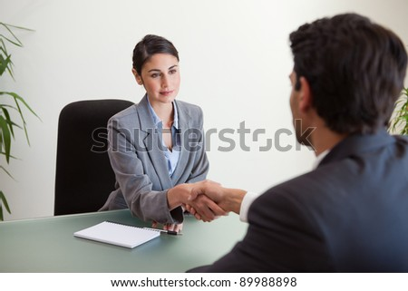 Young manager shaking the hand of a customer in her office