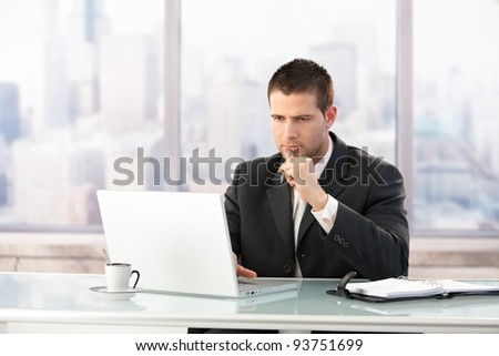 Young manager sitting at desk in bright office, working on laptop.? - stock photo